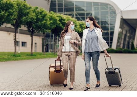 Two Business Women In Protective Masks With Suitcases Go To The Airport. Young Women Near Airport, O