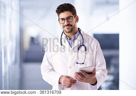 Male Doctor Using Digital Tablet While Standing On The Hospital's Foyer
