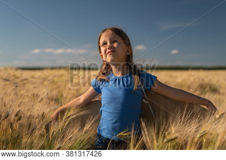 Little girl child in a field in nature with wings and an airplane runs and enjoys life