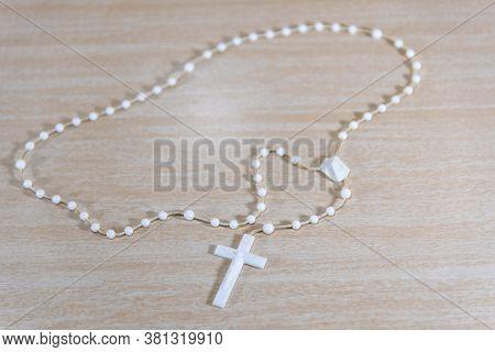 Rosary And White Catholic Crucifix On Light Wooden Background