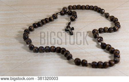 Rosary And Crucifix Symbols Of Catholicism On Light Wooden Background