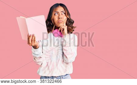 Young beautiful mixed race woman reading a book wearing headphones serious face thinking about question with hand on chin, thoughtful about confusing idea