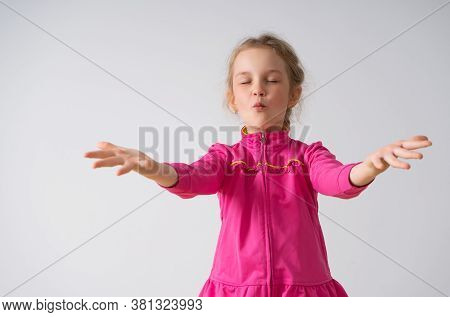 Concentrated Little Girl With Tightly Closed Eyes Playing In Doing Magic Raising Up Hands With Open