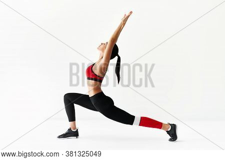 Young Sporty Woman Doing Yoga Asana Warrior I Pose And Stretching On White Background. Practicing Yo