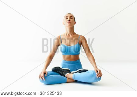 Young Sporty Attractive Woman In Sportswear Practicing Yoga, Meditating In Lotus Pose Padmasana On W