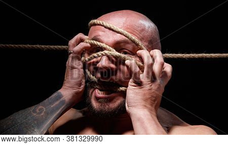 Photo Of Binded Screaming Bald Man With Rope On Face