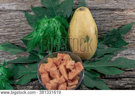 Pieces Of Papaya Papaya (carica Papaya) In Bowl And Fresh Leaves And Fruits In The Background