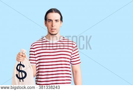 Young adult man with long hair holding money bag with dollar symbol thinking attitude and sober expression looking self confident