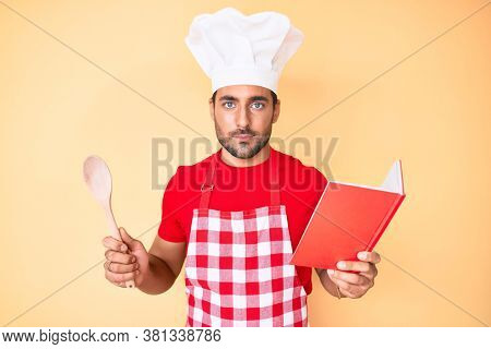 Young hispanic man wearing professional baker apron reading cooking recipe book relaxed with serious expression on face. simple and natural looking at the camera.