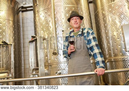 Winemaker with a glass of red wine in front of a stainless steel fermentation tank in the factory