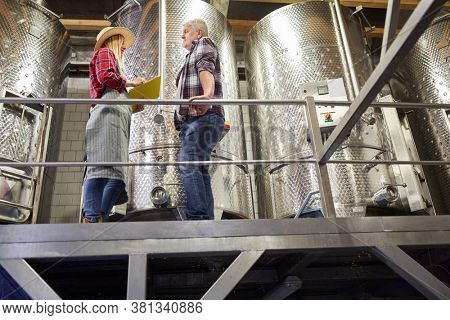 Winemaker and trainee with checklist in front of a fermentation tank in the winery
