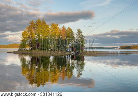 Small island on the lake with country house in Finland. Traditional finnish lake landscape with cottage house and sauna at sunset