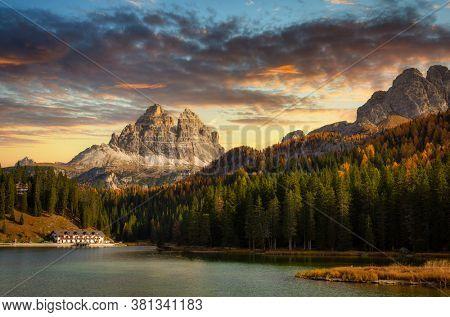 The Tre Cime di Lavaredo mountains (3003 m) and Lago di Misurina lake at sunset. Dolomites, South Tyrol. Italy