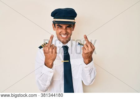 Young hispanic man wearing airplane pilot uniform showing middle finger doing fuck you bad expression, provocation and rude attitude. screaming excited