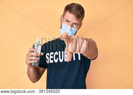 Young caucasian man wearing security t shirt and medical mask holding hand sanitizer gel pointing with finger to the camera and to you, confident gesture looking serious