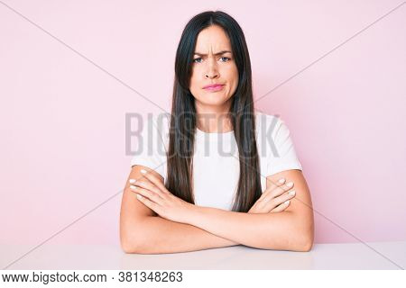 Young caucasian woman sitting at the table wearing casual white tshirt skeptic and nervous, disapproving expression on face with crossed arms. negative person.