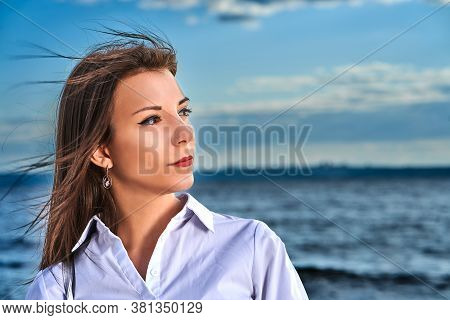 Portrait Of A Young Brunette Girl Against The Background Of The Evening Sky Over The Sea. Close-up O