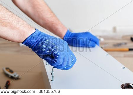 Furniture Assembly. Male Hands In Gloves Master Collects Furniture Using Screwdriver Tools, Instrume