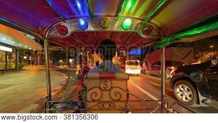 Riding Tuk Tuk Driving On Street Road, Thai Traditional Native Taxi At Night In Bangkok City, Thaila