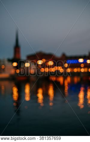 Blurred Background Of Stockholm City At Night. Cityscape Lights Captured With Reflection On The Rive