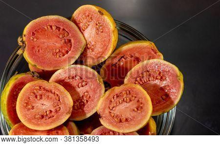 Guava Fruits (psidium Guajava) In Halves In Bowl On Dark Background