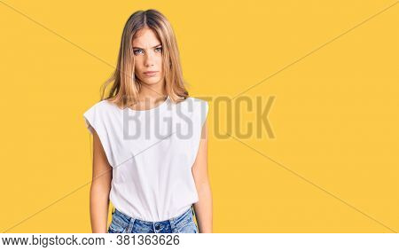Beautiful caucasian woman with blonde hair wearing casual white tshirt skeptic and nervous, frowning upset because of problem. negative person.
