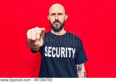 Young handsome man wearing security t shirt pointing with finger to the camera and to you, confident gesture looking serious