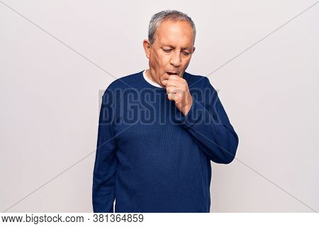 Senior man with grey hair wearing casual sweater feeling unwell and coughing as symptom for cold or bronchitis. health care concept.