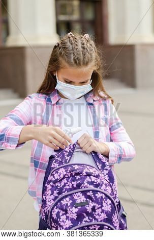 Little Girl Child With Face Mask And Sanitizer. Education Concept. Back To School After Covid-19.  P