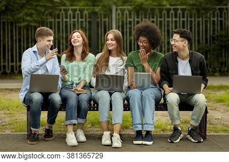Group Of College Students With Laptops And Tablet Pc Studying Outdoors, Sitting On Bench At Campus,