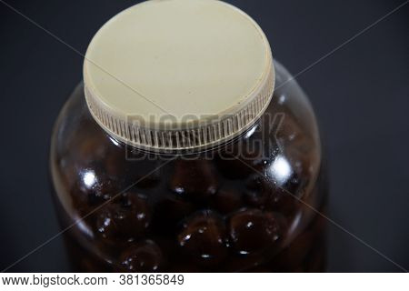 Glass Container With Brandy Liquor Soaked In Butiá Fruits (butia Capitata)