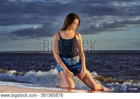 Young Brunette Girl Kneels On The Sandy Shore. Summer Sunny Evening.