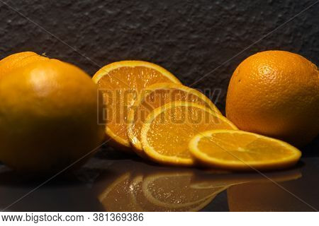 Fruits Cut From Orange (citrus Sinensis) And Sliced On Dark Background
