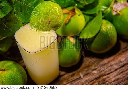 Fruits And Passion Fruit Juice (passiflora Edulis) Amid Green Leaves On Wooden Background