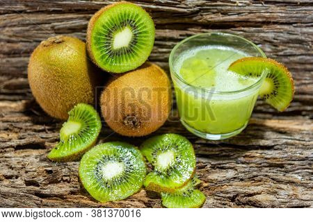 Fruits And Kiwi Juice Fresh And In Halves On A Woody Background