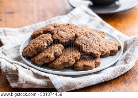 Sweet cookies. Crunchy chocolate biscuits shape flower on plate.