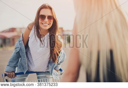 Cheerful Young Female In Denim Outfit And Trendy Sunglasses With Pushcart Chatting With Unrecognizab