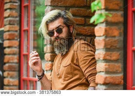 Man Smoking A Cigarette. Business Man In Glasses Smoking Cigarette On Street. Go Out For Smoke Break