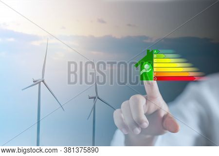 Energy Efficiency And Green Energy Concept, Woman Hand Touch Energy Efficiency Symbols With Wind Tur