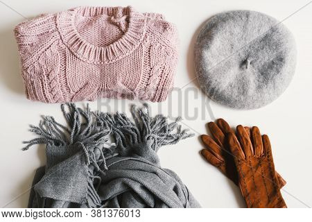 Handmade Knitted Sweater, Gray Scarf, Beret Hat, Suede Gloves On White Background, Top View. Winter