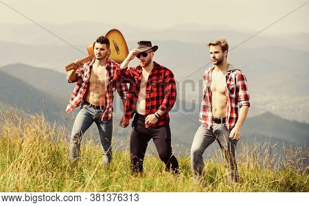 Friendly Guys With Guitar Hiking On Sunny Day. Tourists Hiking Concept. Hiking With Friends. Enjoyin