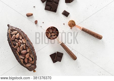 Flat Lay Composition With Cocoa Beans, Chocolate Pieces, Cocoa Powder And Pods On White Concrete Bac