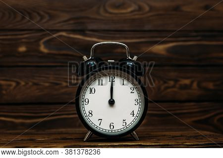 Clock On A Wooden Background. The Clock Shows The Time Of Twelve O'clock In The Afternoon. Clock Sho