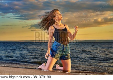 Young Brunette Girl  Kneels On The Sandy Shore Of Sea.