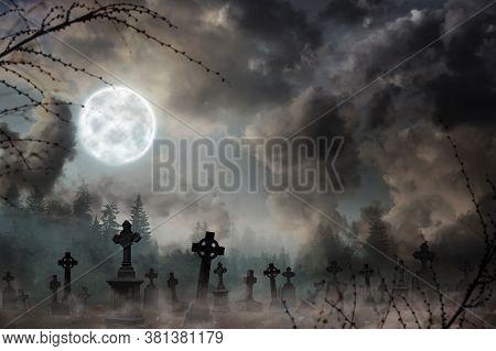 Misty Graveyard With Old Creepy Headstones Under Full Moon On Halloweeen