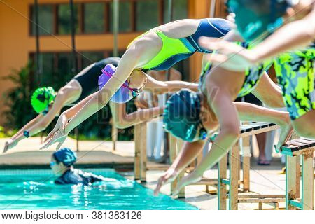 Chiang Mai, Thailand - 10 October 2019 - Young Female Swimmers Dive Off The Platform Into The Swimmi
