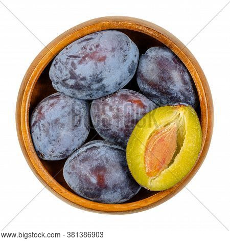 Ripe European Plums With Cross Section Of One Fruit In A Wooden Bowl. Freestone Fruit With Purple, V