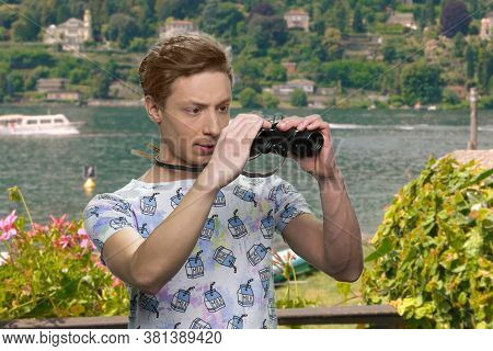Teen Boy Observing Sea With Binoculars. Beautiful Nature In The Background. People, Holidays And Sum