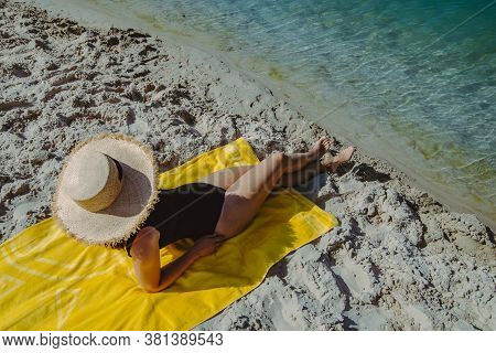 Woman Laying On Yellow Blanket Sunbathing At Sand Beach