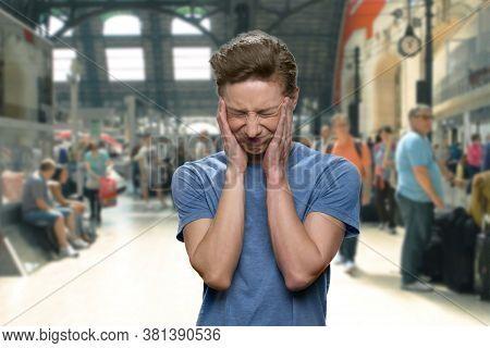 Stressed Teenage Boy Suffering From Headache. Airport Blurrred Background Interior.